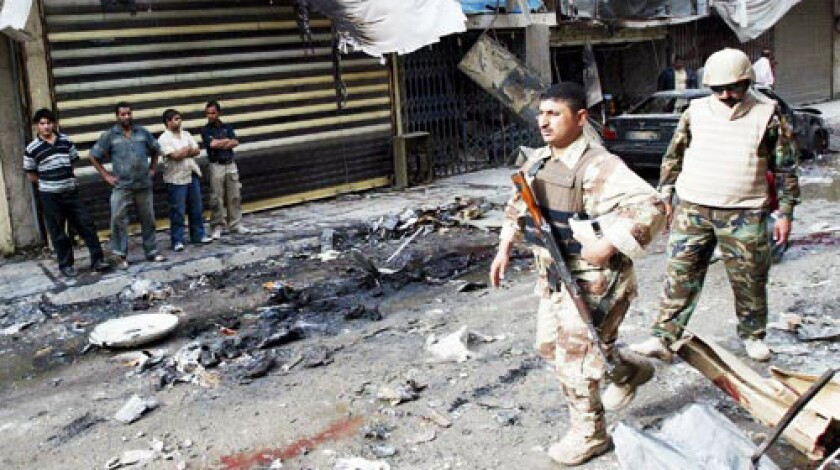 Iraqi soldiers take stock of the damage after a car bomb exploded near the popular Tahrir Square market in central Baghdad. The attack killed 18 people.