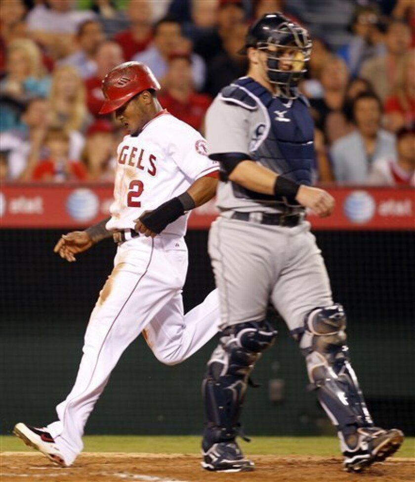 Los Angeles Angels' Erick Aybar (2) scores a run on a sacrifice bunt by Jeff Mathis as Seattle Mariners catcher Adam Moore, right, watches during the sixth inning of their baseball game in Anaheim, Calif., Friday, Sept. 10, 2010. (AP Photo/Lori Shepler)