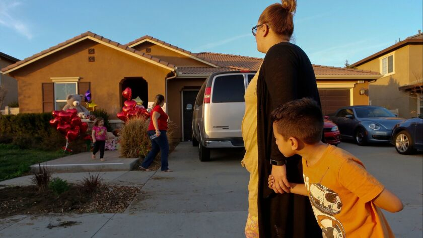 File - In this Jan. 18, 2018 file photo, neighbor Avery Sanchez, 6, peeks behinds his mother, Liza T