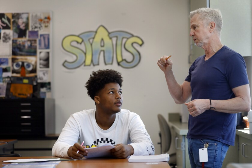 "Robert Moore, 17, looks up at Robert Montgomery, who teaches ""Transition to College Mathematics and Statistics,"" in a classroom at Roybal Learning Center."