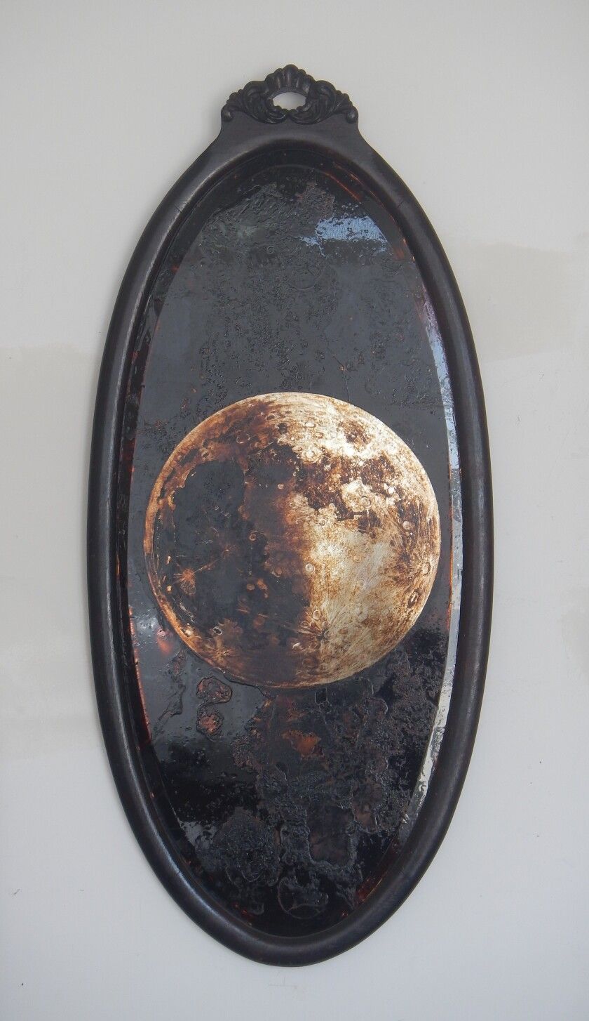 """""""Moon -- Reflector"""" by James Griffith, 2018. Tar on antique mirror, 44 inches by 21 inches"""
