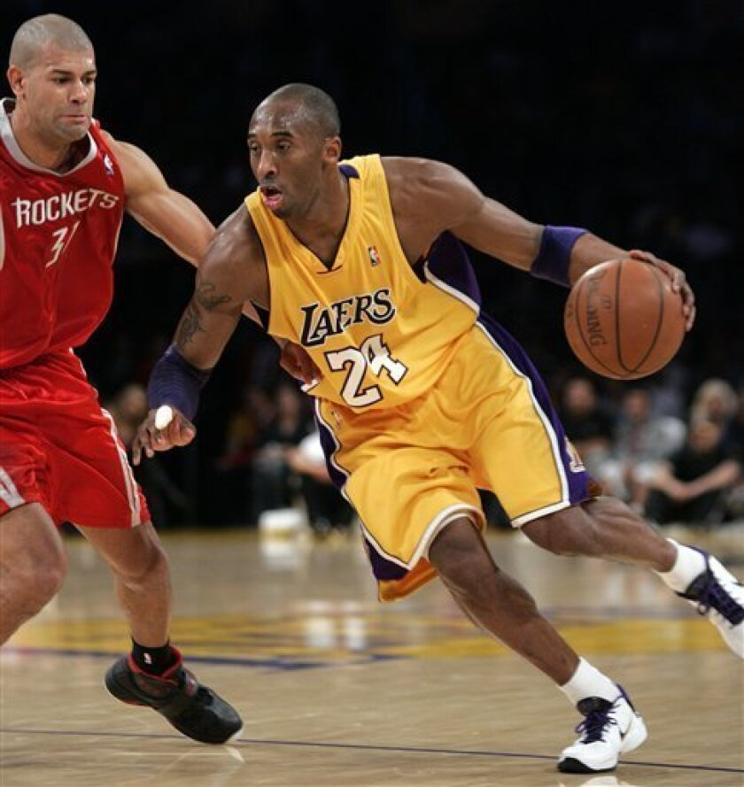 Los Angeles Lakers guard Kobe Bryant (24) drives against Houston Rockets guard Shane Battier in the first half of an NBA basketball game in Los Angeles, Tuesday, Jan. 5, 2010. (AP Photo/Jason Redmond)