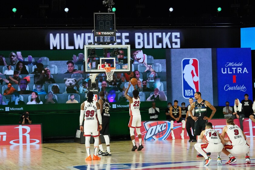 Bucks fans watch Heat star Jimmy Butler shoot free throws during Game 2 of their playoff series.