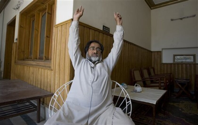In this photo taken on Wednesday, April 13, 2011, Abdul Hameed demonstrates how he had been ordered to put his hands up by intelligence agents at his house in Abbottabad, Pakistan from where Indonesian al-Qaida-linked militant, Umar Patek, was arrested in Jan. 2011. Patek was on the run from a $1 million U.S. bounty on his head, for allegedly helping mastermind the 2002 suicide bombings of nightclubs in Bali that killed 202 people. (AP Photo/Anjum Naveed)