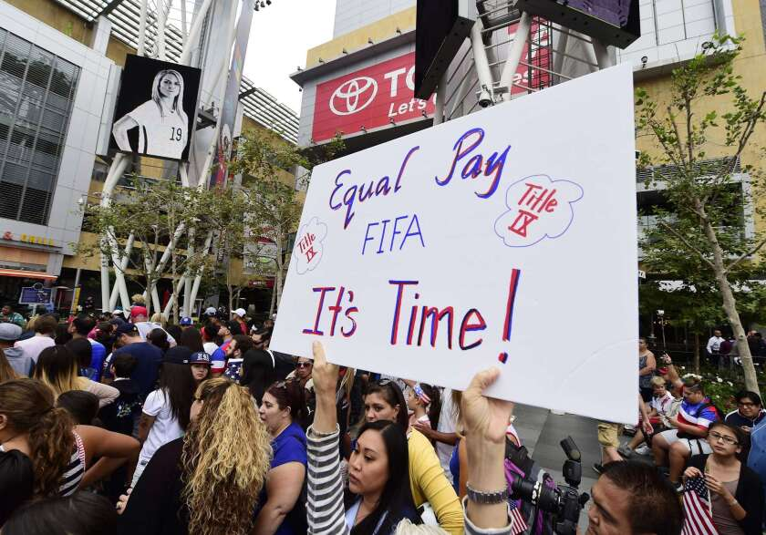 A soccer fan holds up a sign calling for equal pay for female athletes at the U.S. Women's World Cup football team's championship celebration rally at L.A. LIVE in downtown Los Angeles in July.