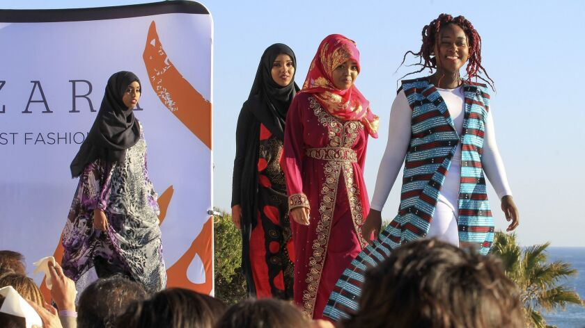 Refugee Girls Academy members, from left, sisters Sumya and Zuhur Ahmed of Kenya, Ayan Yusuf of Somalia and Nangolie Lembe of Congo walk the catwalk in their cultural costumes at the Artizara fashion show in Leucadia on Sunday.