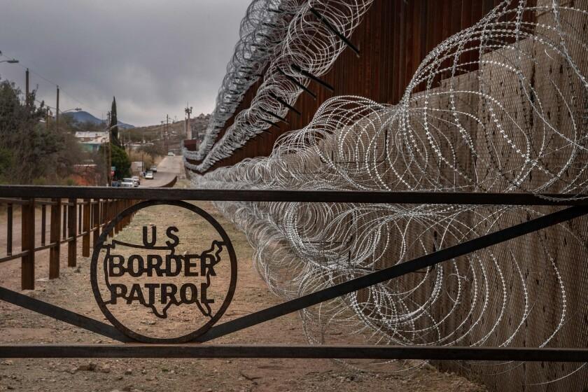 Una cerca de metal marcada con el signo de la Patrulla Fronteriza de los EE. UU. evita que las personas se acerquen al alambre de púas, concertina, que cubre la cerca de la frontera de los EE. UU. y México, en Nogales, Arizona, el 9 de febrero de 2019.