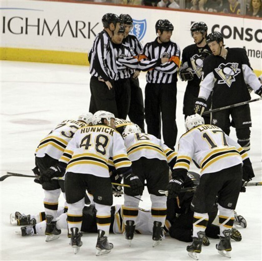 The Boston Bruins lean over fallen teammate Marc Savard after a hit in the third period of an NHL hockey game against the Pittsburgh Penguins in Pittsburgh, Sunday, March 7, 2010. Savard was taken from the ice on a stretcher. The Penguins won 2-1. (AP Photo/Keith Srakocic)