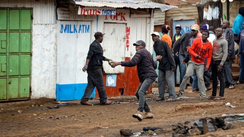 Protesters throw rocks at riot police during clashes in the Kawangware slum of Nairobi, Kenya. International observers on Thursday urged Kenyans to be patient as they awaited final election results.