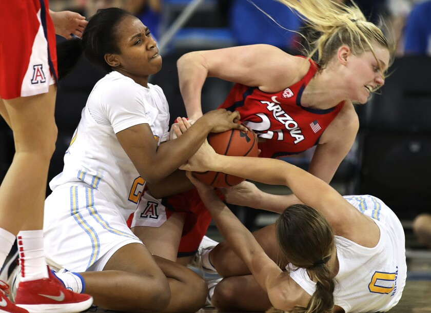 UCLA's Charisma Osborne, left, and Chantel Horvat, right, fight for the ball with Arizona's Cate Reese during the Bruins' win Sunday.
