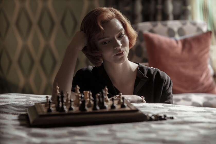 """Anya Taylor-Joy as Beth Harmon looks at a chess board in """"The Queen's Gambit."""""""