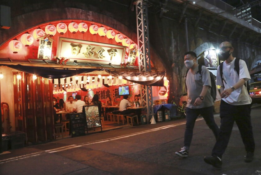 مردان نقابدار از کنار یک رستوران با نور زیاد در خیابانی در توکیو عبور می کنند