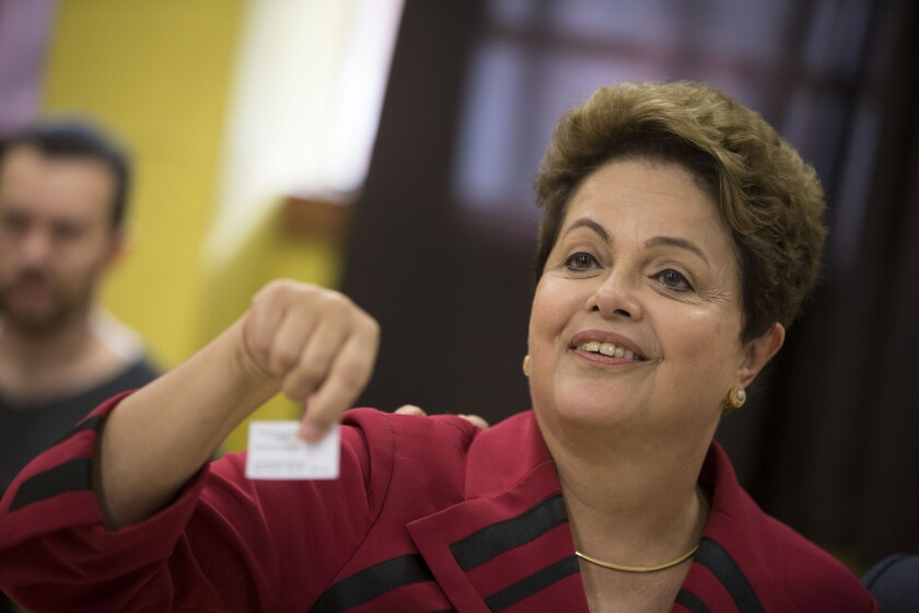 Brazilian President Dilma Rousseff, who is running for reelection, shows her electronic voting receipt after voting Sunday in Porto Alegre.