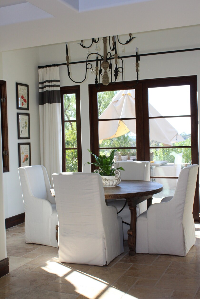 Darkly stained baseboards, dining table and window frames illustrate the idea of vertical ribboning.