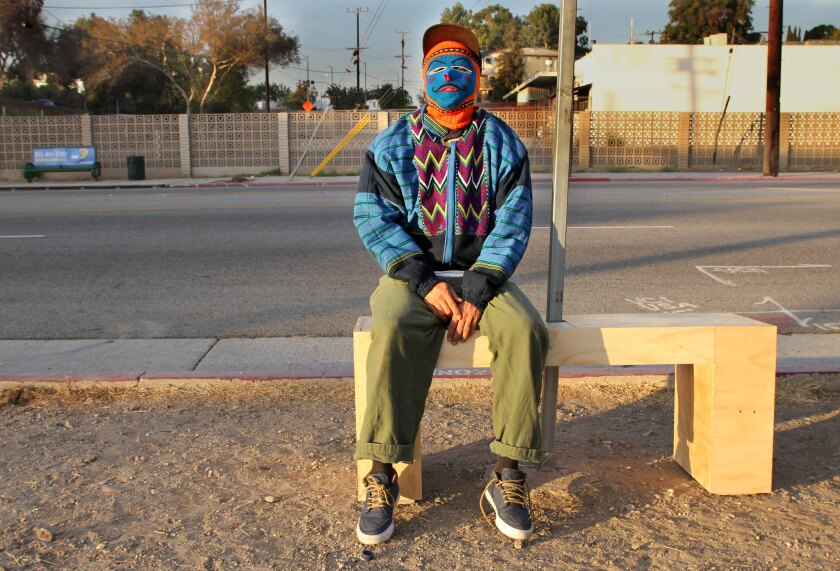 An artist who prefers to stay anonymous artist poses on his freshly installed bench on Valley Boulevard east of downtown. The installations point to poor transit infrastructure in working-class areas. His bench was gone in five days.
