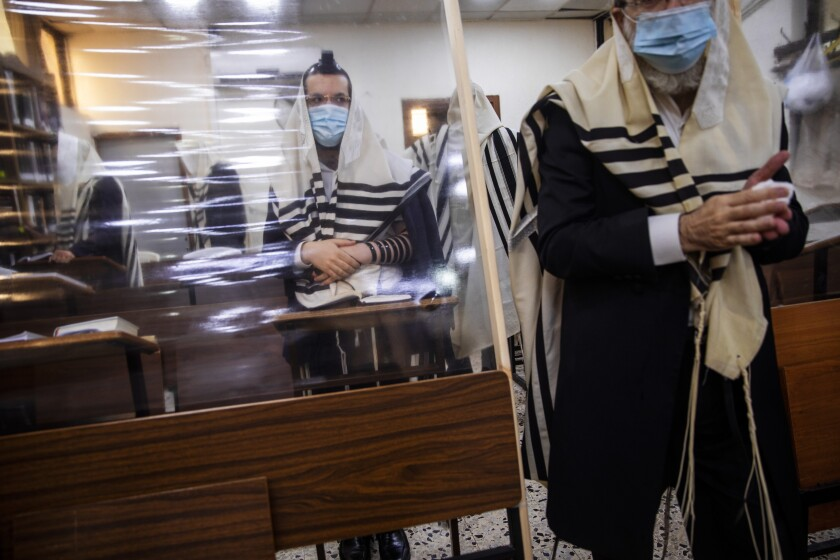 Ultra-Orthodox Jews pray in a synagogue separated by a plastic partition in Bnei Brak, Israel, on Friday.