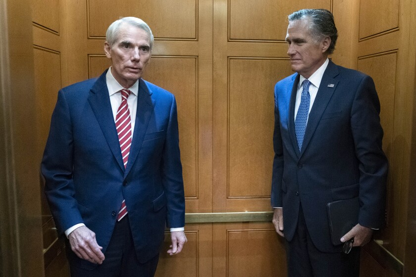 Sen. Rob Portman, R-Ohio, left, accompanied by Sen. Mitt Romney, R-Utah, leave in the elevator after a closed door talks about infrastructure on Capitol Hill in Washington Thursday, July 15, 2021. (AP Photo/Jose Luis Magana)