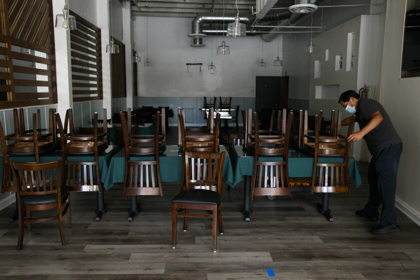 Fabian Nahui, the owner of a Peruvian restaurant, arranges chairs Monday, July 6, 2020, in Los Angeles.