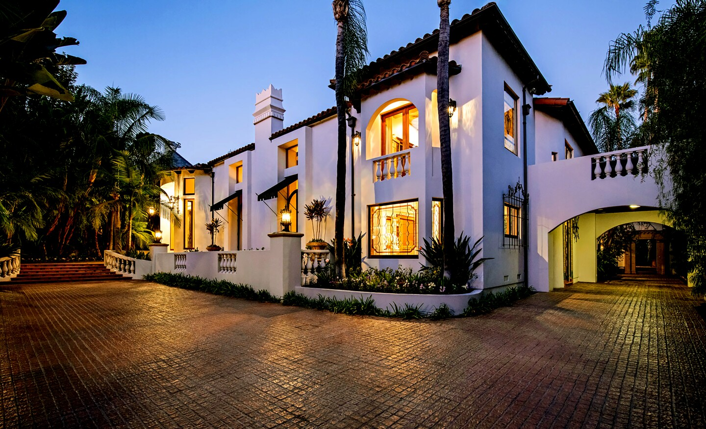 The Wallace Neff-designed house in the flats of Beverly Hills sits on more than a third of an acre surrounded by lush landscaping. Listed for $15.75 million, the Spanish Colonial Revival-style house showcases spectacular original woodwork and bright tile risers. Two kitchens and a screening room are among updates made to the house, which has six bedrooms and nine bathrooms. In the living room, arched French doors bookend a dramatic wall fireplace, while hand-stenciled beams top the space.