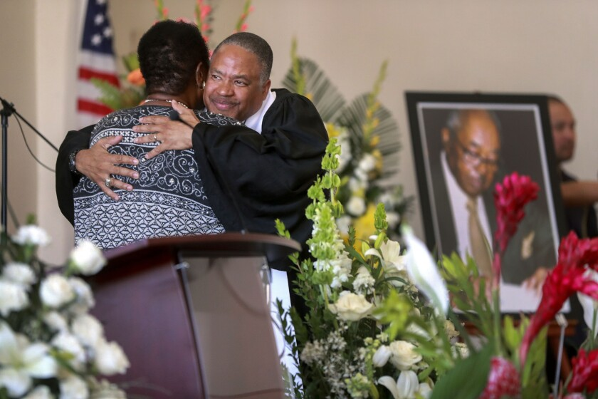Pastor Nathan Byrd hugs Dr. Dorothy Smith after she spoke during a memorial service for Reverend George Walker Smith, pictured at right, at the Christ United Presbyterian Church on Friday March 6, 2020 in San Diego, California.