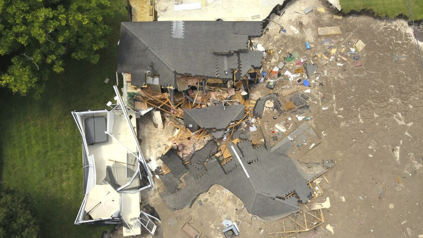 In this aerial photo, debris is strewn about after a sinkhole damaged two homes in Land O' Lakes, Fla. on July 14, 2017.