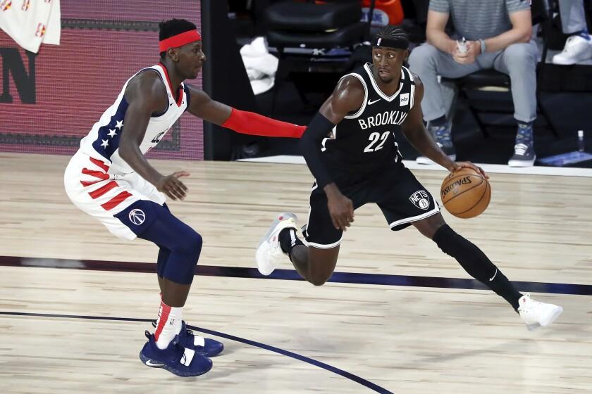 Brooklyn Nets guard Caris LeVert (22) dribbles against Washington Wizards forward Isaac Bonga (17) in the first half of an NBA basketball game Sunday, Aug. 2, 2020, in Lake Buena Vista, Fla. (Kim Klement/Pool Photo via AP)
