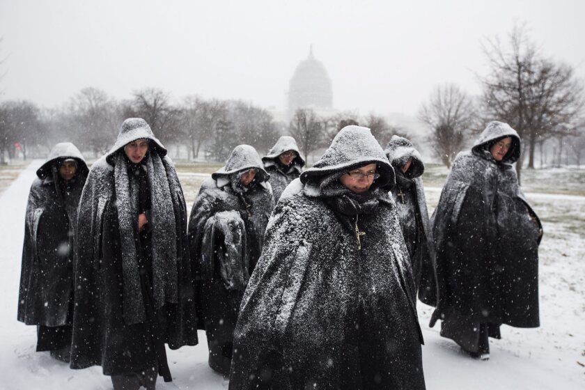 Nuns visiting Washington from a Chicago convent walk through the snow.