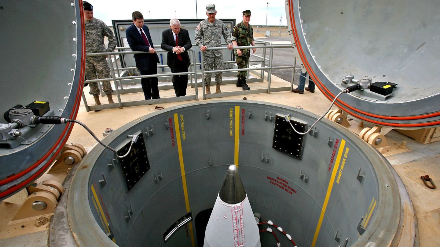 Then-Defense Secretary Robert M. Gates, center, and then-Sen. Mark Begich (D-Alaska), second from left, inspect a rocket interceptor in its silo at Ft. Greely in 2009.
