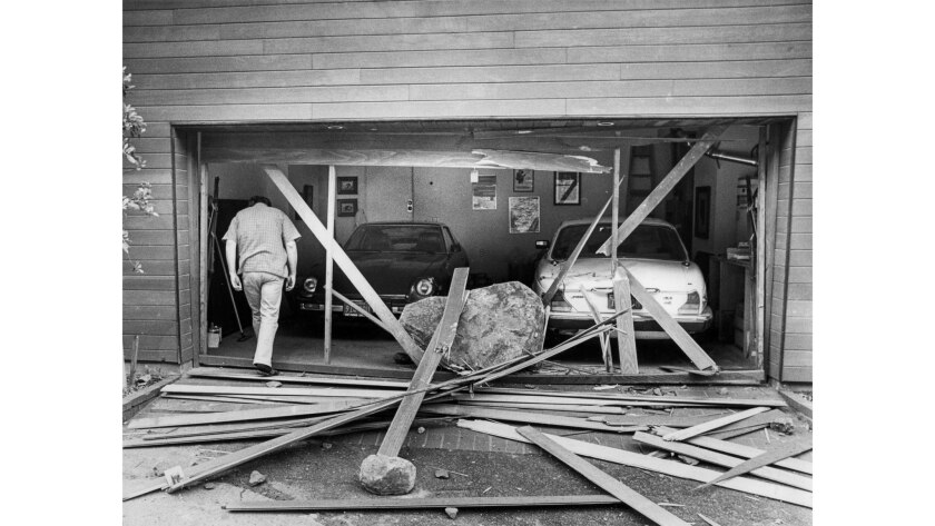 March 24, 1983: Robert Tellier, owner of a home on 19700 block of Pacific Coast Highway, enters the garage where a boulder crashed through the door, damaging both cars.