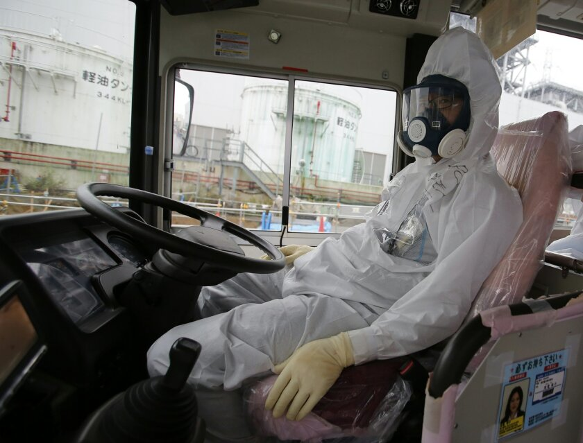 A driver wearing protective gears rests on a bus at the Fukushima Dai-ichi nuclear power plant in Okuma, Fukushima prefecture, northeastern Japan, Wednesday, Nov. 12, 2014. More than three years into Japan's massive cleanup of the tsunami-damaged nuclear power plant, only a tiny fraction of the workers are focused on the key tasks such as preparations for dismantling the broken reactors and removing radioactive fuel rods. Instead, nearly all the workers are devoted to a single, enormously distracting problem: coping with the vast amount of contaminated water - mixture of underground water running into the recycled water that becomes contaminated and leaks after being pumped into the damaged reactors to keep their melted cores from overheating. (AP Photo/Shizuo Kambayashi, Pool)