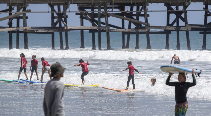Kids ride a wave together as they learn to surf on a summer day at the San Clemente Pier Tuesday.
