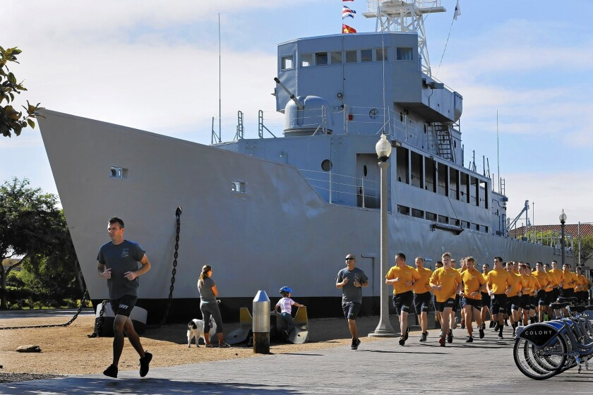 "Navy personnel jog past the Recruit, nicknamed the ""Neversail,"" in San Diego. It is the only commissioned ship in the Navy that never touched water."