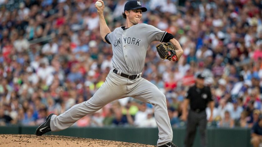 In this July 17, 2017, file photo, Yankees starting pitcher Bryan Mitchell throws to the Minnesota Twins in the third inning of a baseball game, in Minneapolis. Third baseman Chase Headley and pitcher Bryan Mitchell have been traded by the Yankees to the Padres on Dec. 12, 2017.