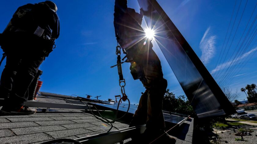 Contractors install a solar energy system at a home in Van Nuys.