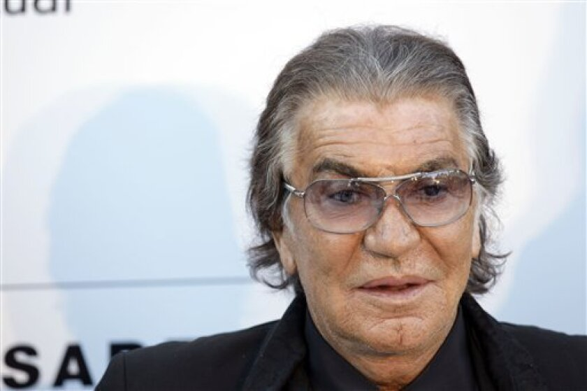 FILE - In this May 10, 2010 file photo, designer Roberto Cavalli arrives for the amfAR Cinema Against AIDS benefit at the Hotel du Cap-Eden-Roc, during the 63rd Cannes international film festival, in Cap d'Antibes, southern France. The Italian designer with a penchant for animal prints likes to blog about his daily happenings and includes photos of his travels, and beloved German Shepard puppy, Lupo. (AP Photo/Joel Ryan, file)