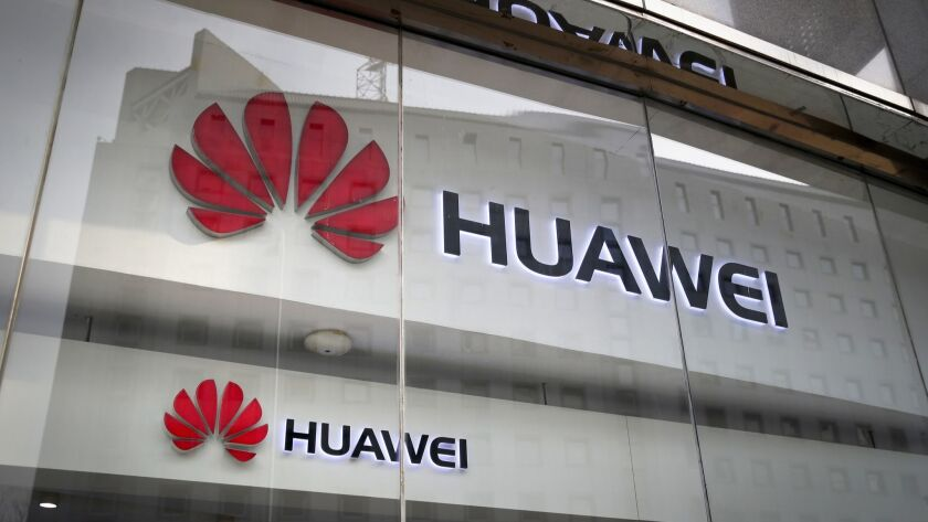 Huawei logos are displayed at its retail shop window reflecting the Ministry of Foreign Affairs office in Beijing.