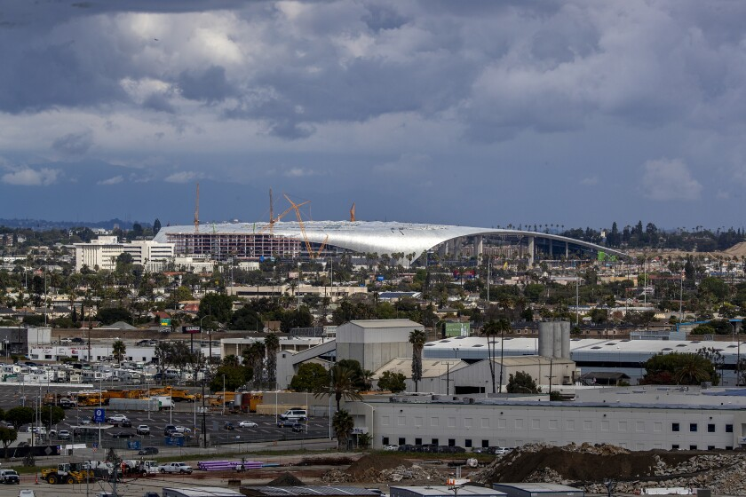 Construction workers work on the SoFi Stadium in Inglewood, where the Rams and Chargers will be playing next season.