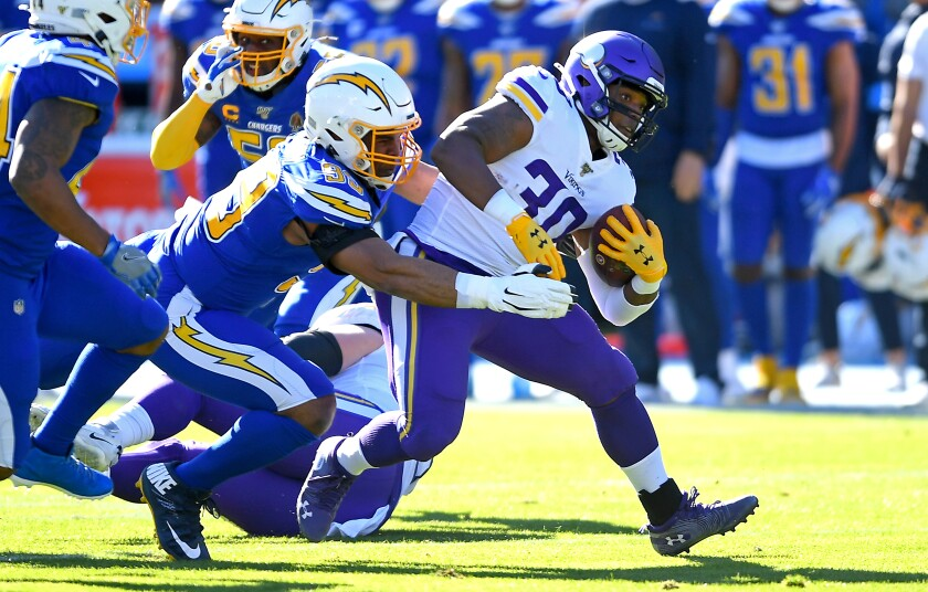 Chargers safety Derwin James, left, tackles Minnesota Vikings fullback C.J. Ham during a game on Dec. 15.