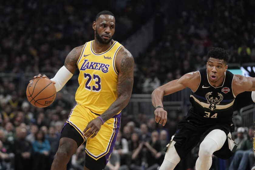 The Lakers' LeBron James dribbles past the Bucks' Giannis Antetokounmpo on Thursday in Milwaukee.