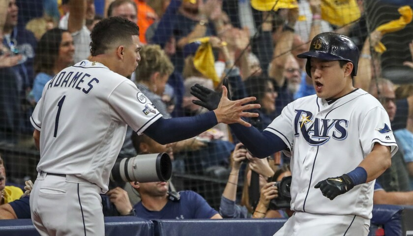 Tampa Bay Rays first baseman Ji-Man Choi (26), right, celebrates scoring along with shortstop Willy Adames (1) after Choi scored on a single in the first inning against the Houston Astros in Game 4 of the ALDS on Tuesday in St. Petersburg, Fla.
