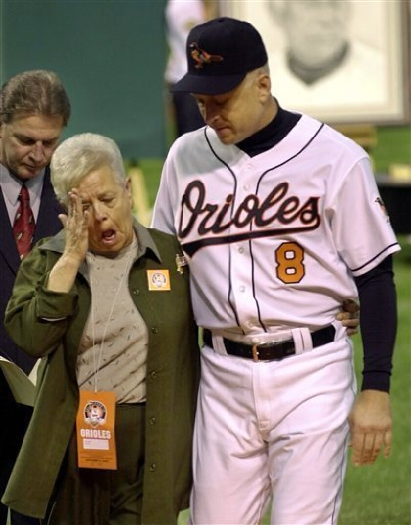 FILE - This Oct. 6, 2001 file photo shows Cal Ripken escorting his mother, Vi, from the field, after throwing out the ceremonial first pitch before Cal's final game, at Oriole Park in Baltimore. Police say Cal Ripken Jr.'s mother is safe after an armed man abducted her from her home northeast of Ba