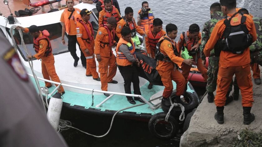 Indonesian search and rescue workers carry a victim's body after a ferry sinking at Tigaras port in Lake Toba, North Sumatra, on Wednesday.