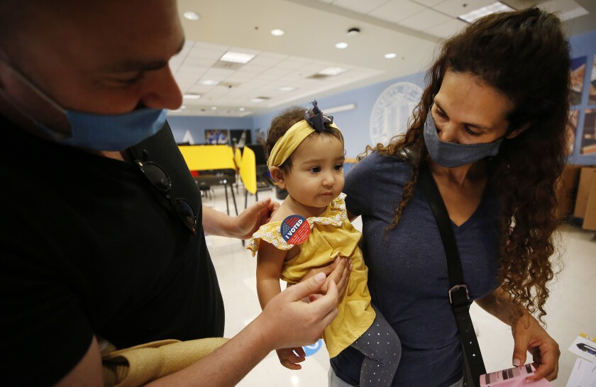 """A woman carries a child with a """"I voted"""" sticker on her. A man is next to them."""