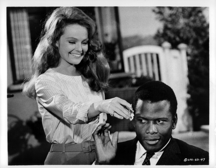 "Katharine Houghton puts a flower in Sidney Poitier's hair in a scene from the 1967 film ""Guess Who's Coming to Dinner."""