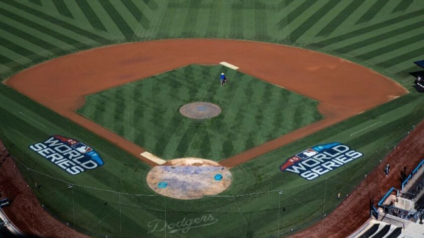 A grounds crew member gets his grass lines in sync on the field for Friday's Game 3 of the World Series at Dodger Stadium.
