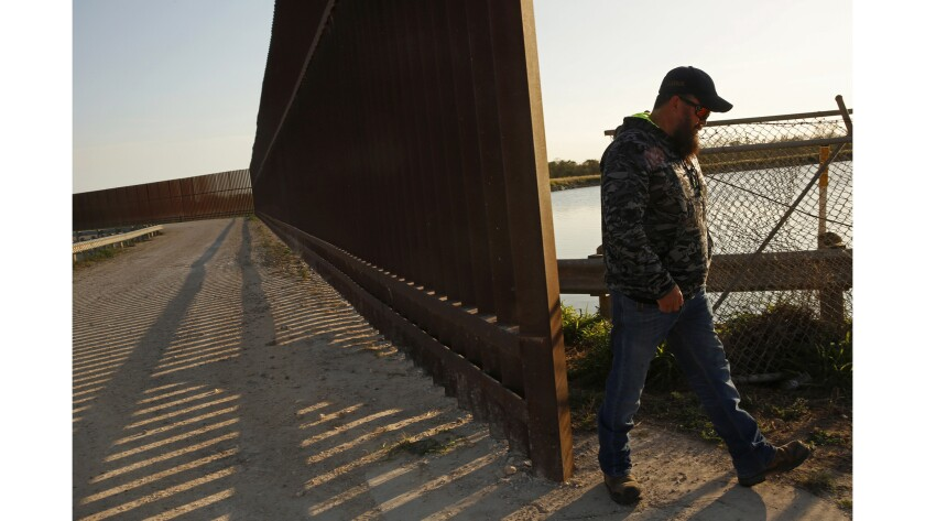 Robert Cameron stands on the south side of the border fence in Progreso Lakes, where he does tours for people who want to see the border area.
