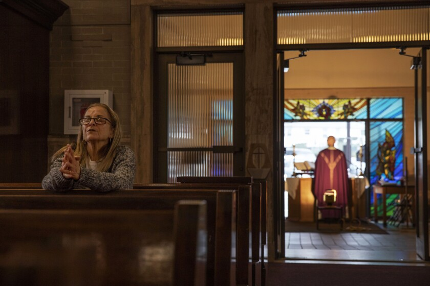 FILE - Fran DiBiasio sits alone in Our Lady of Grace Catholic Church as Rev. Peter Gower celebrates Mass from the front door as worshippers listen over the radio from their cars in the parking lot, Sunday, March 29, 2020, in Johnston, R.I. For the first time in nearly two decades, only half of U.S. households donated to a charity, according to a study released Tuesday, July 27, 2021. Experts say many factors are contributing to the decline. The percentage of Americans who give to religious causes has decreased in tandem with attendance at worship services as the number of Americans not affiliated with any religion grows. (AP Photo/David Goldman, File)
