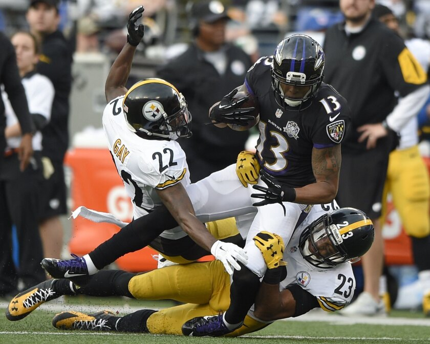 Baltimore Ravens wide receiver Chris Givens (13) is stopped by Pittsburgh Steelers cornerback William Gay (22) and free safety Mike Mitchell (23) during the second half of an NFL football game in Baltimore, Sunday, Dec. 27, 2015. (AP Photo/Nick Wass)