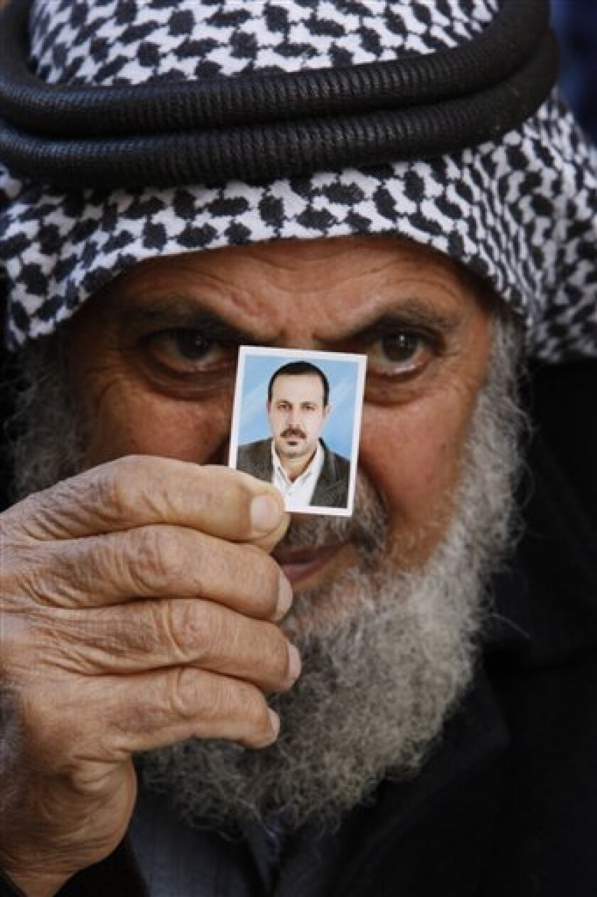 The father of Palestinian militant Mahmoud al-Mabhouh, who was recently killed, holds up a family photo showing al-Mabhouh, at their home in the Jebaliya refugee camp, northern Gaza Strip, Friday, Jan. 29, 2010. Hamas claimed on Friday that Israeli agents assassinated one of the Palestinian militant group's veteran operatives in a killing allegedly carried out last week in Dubai, and vowed to retaliate. (AP Photo/Hatem Moussa)