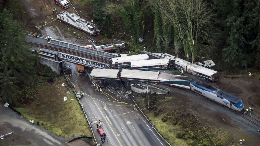 Cars from an Amtrak train lie on Interstate 5 in DuPont, Wash., after derailing.